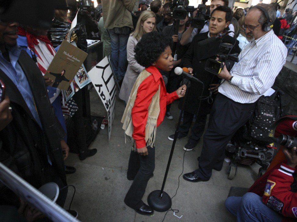 A young Michael Jackson impersonator performs outside the courthouse