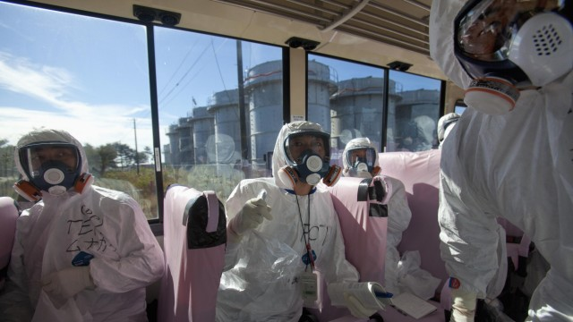 Officials from TEPCO and Japanese journalists look at the crippled Fukushima Daiichi nuclear power plant from a bus in Fukushima