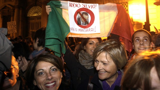 A woman holds up an Italian flag with displaying a picture of outgoing Prime Minister Silvio Berlusconi in front of the Presidential palace in Rome
