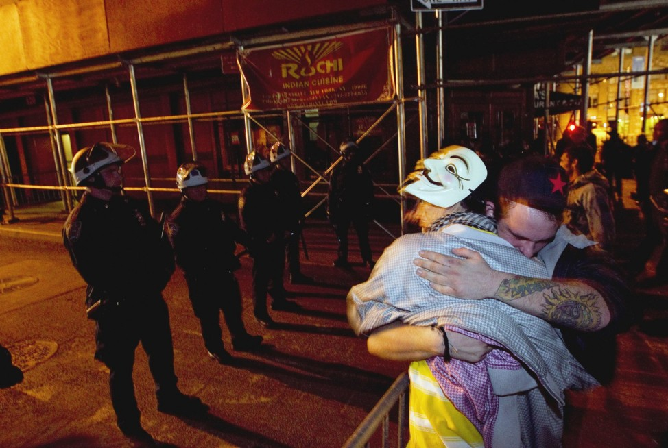 Members of the Occupy Wall St movement embrace each other after being removed from Zuccotti Park in New York