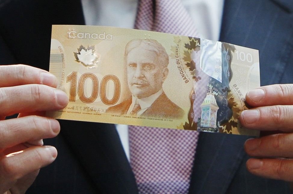 Carney holds the new Canadian 100 dollar bill made of polymer in Toronto