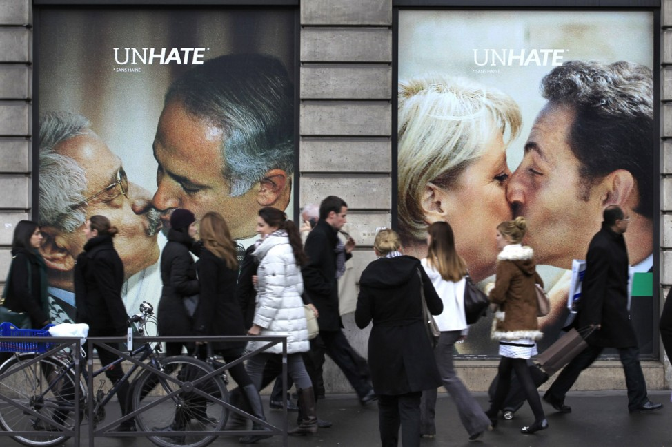 People walk past Benetton billboards of world leaders kissing each other on the mouth in Paris