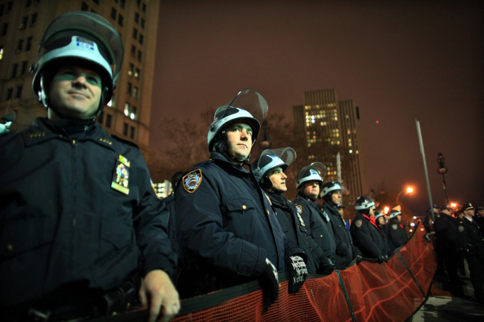 N.Y. City police officers keep an eye on protesters affiliated with the Occupy Wall Street movement at the beginning of Brooklyn bridge in New York