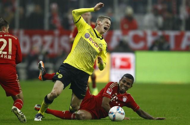 Gustavo of Bayern Munich fouls Piszczek of Borussia Dortmund during their German first division Bundesliga soccer match in Munich