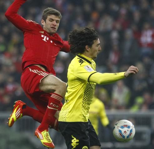 Mueller of Bayern Munich challenges Hummels of Borussia Dortmund during their German first division Bundesliga soccer match in Munich