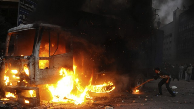 Protester sets fire to a riot police vehicle during clashes at Tahrir Square in Cairo