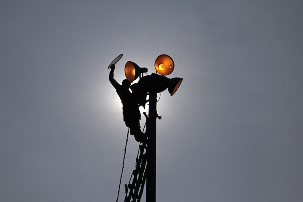 A worker is silhouetted as he repairs streetlights at a park in Lahore