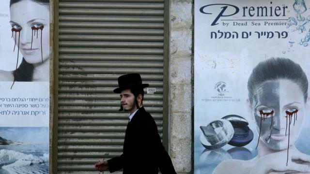 An Ultra Orthodox Jewish man walks past a vandalized poster showi