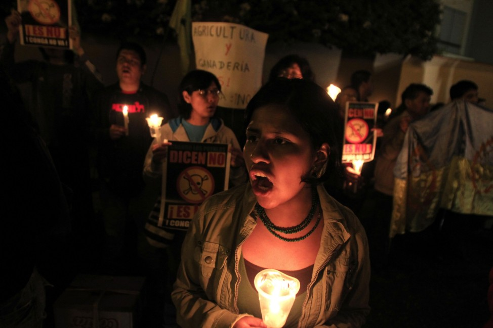 Demonstrators hold candles as they shout slogans during a protest against Newmont's proposed $4.8 billion Conga gold mine in Cajamarca, in Lima