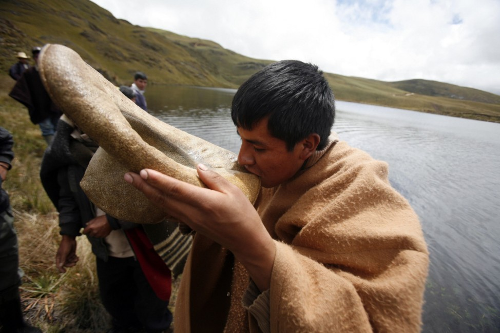 An Andean drinks water from the Cortada lagoon during a protest against Newmont's proposed $4.8 billion Conga gold mine