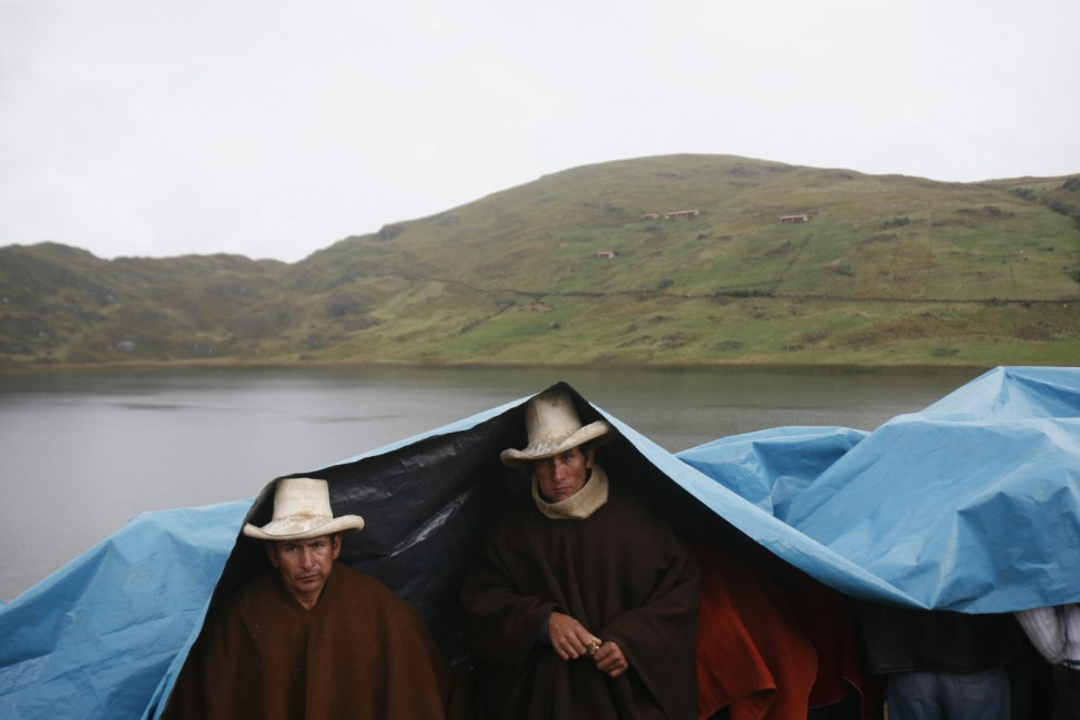Andean people take shelter from the rain during an assembly after a march against Newmont's proposed $4.8 billion Conga gold mine, in front of the El Perol lagoon in Cajamarca