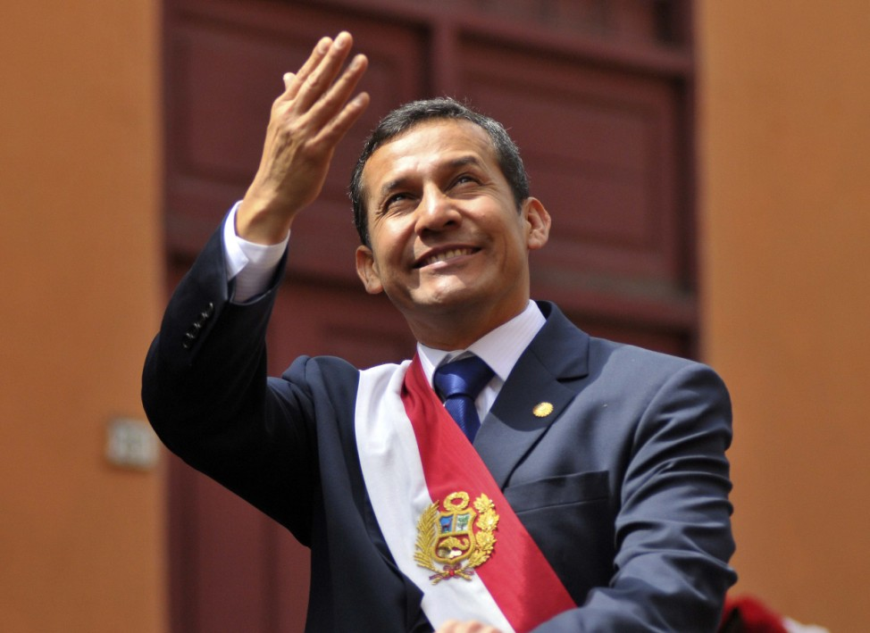 Peru's President Ollanta Humala waves from the back of a vehicle as he rides from Congress to the presidential palace in Lima