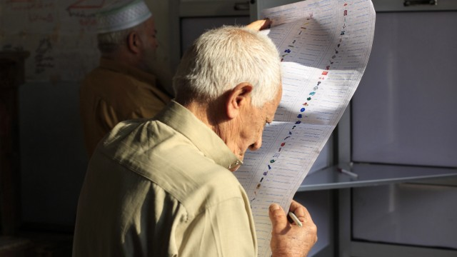 An old man reads a ballot paper before casting his vote at a polling station during parliamentary elections in Cairo