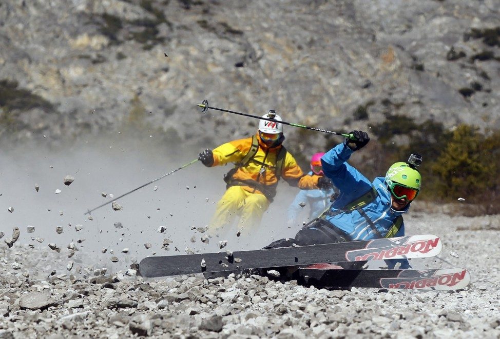 Freeride skiers carve their way down a steep slope of crushed rocks in Haiming