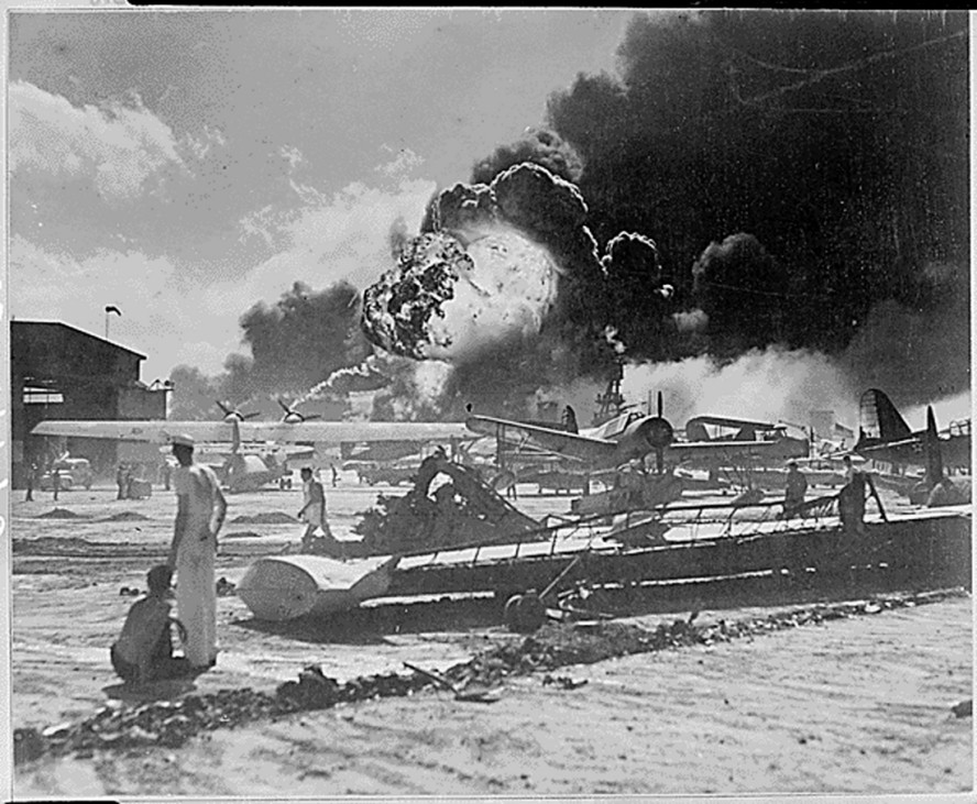 Members of the U.S. Military stand near airplane wreckage during the surprise Japanese aerial attack at Naval Air Station at Pearl Harbor in Hawaii