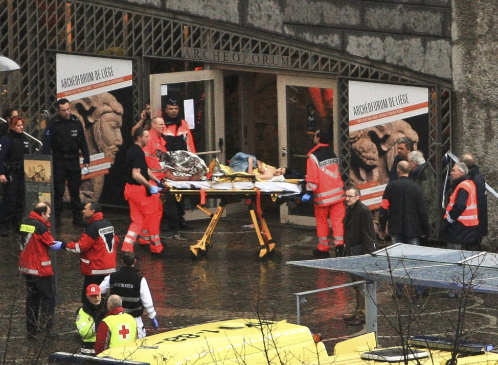 Rescuers evacuate injured people at the Place Saint Lambert square where two men threw explosives in the city center of the Belgian city of Liege