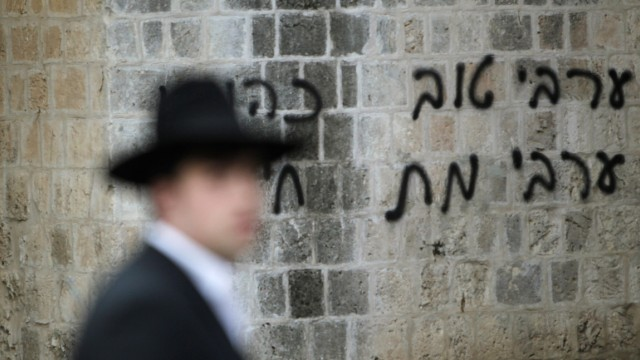 An ultra-Orthodox Jew walks past graffiti sprayed on the outside of a mosque in Jerusalem