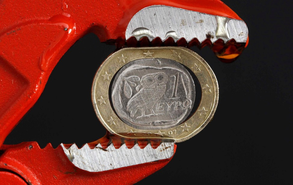 File photo Illustration shows a one Euro coin squeezed by a pair of grips in Athens