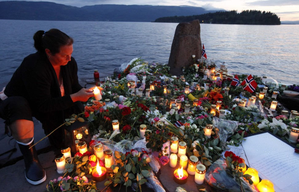 A woman lights a candle to pay her respects to the victims of the shooting spree and bomb attack in Norway, on the shore in front of Utoeya island