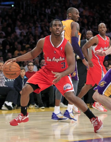 Lakers' Bryant looks back as Clippers' Paul controls the ball during their NBA preseason game in Los Angeles