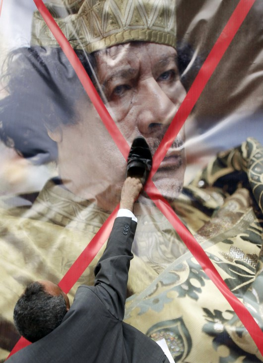 File photo of a Libyan protester using a shoe to hit a crossed-out picture of Gaddafi during a demonstration outside the Libyan Embassy in Cairo