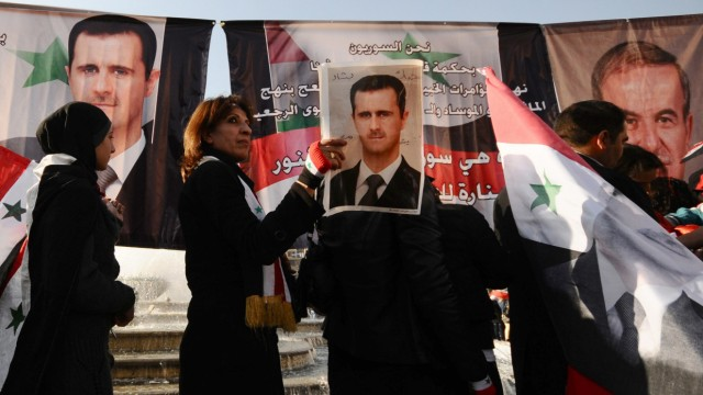 Supporters of Syria's President Bashar al-Assad carry his pictures and Syrian flags during a rally at al-Sabaa Bahrat square in Damascus
