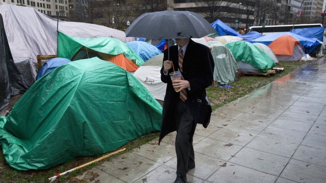 A man walks past the Occupy DC tent camp during the morning rush hour at McPherson Square in Washington