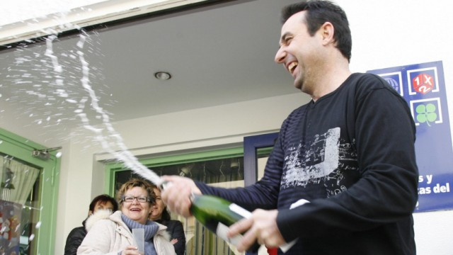 People celebrate having won a portion of the winning lottery number in Spain's Christmas Lottery 'El Gordo' in Granen