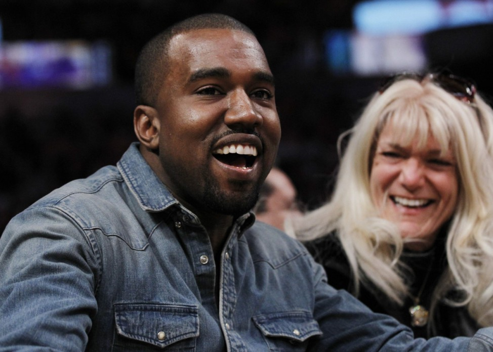 Recording artist Kanye West smiles as he sits courtside while attending the NBA basketball game between the Los Angeles Lakers and Chicago Bulls in Los Angeles