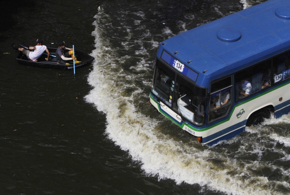 File photo of residents travelling on a boat as a bus drives on a flooded street in Bangkok