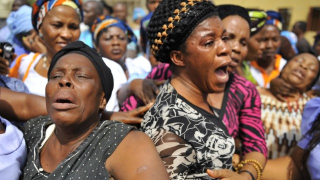 Women weep over their loved ones who died in the Christmas day bomb explosion at St. Theresa's Catholic church in Madalla