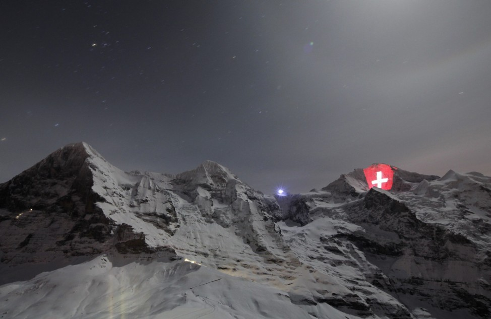 A giant light installation of the flag of Switzerland, by Swiss artist Gerry Hofstetter, illuminates the north face of the Jungfrau mountain, in the Bernese Oberland