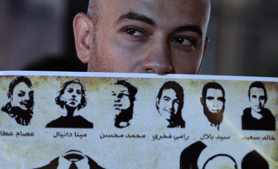 A man holds up a poster of victims killed during the revolution at Talaat Harb Square, in Cairo