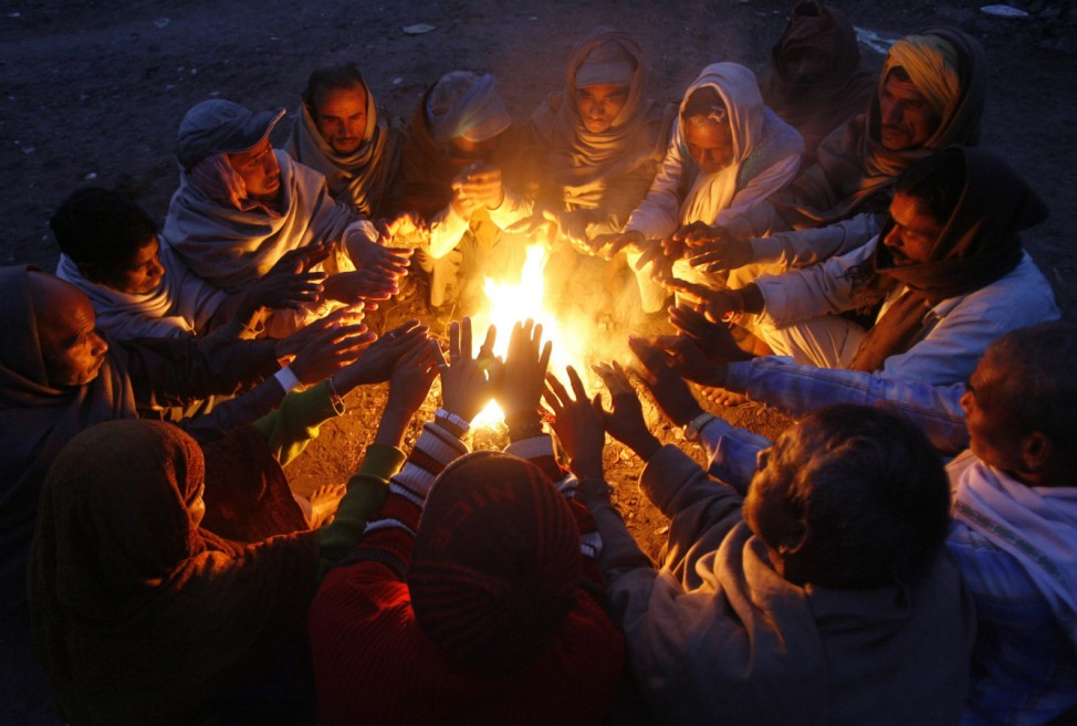 Men warm themselves by a fire at a railway yard on a cold winter morning in Chandigarh