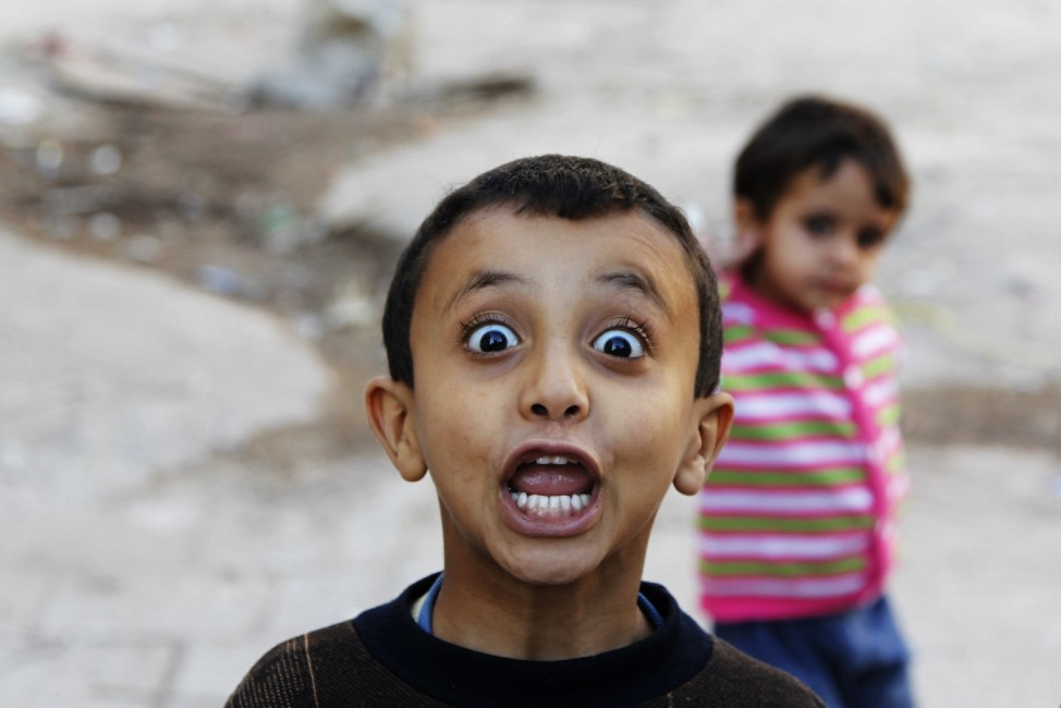 A boy reacts to the camera as he plays in an alley at the Old Sanaa city