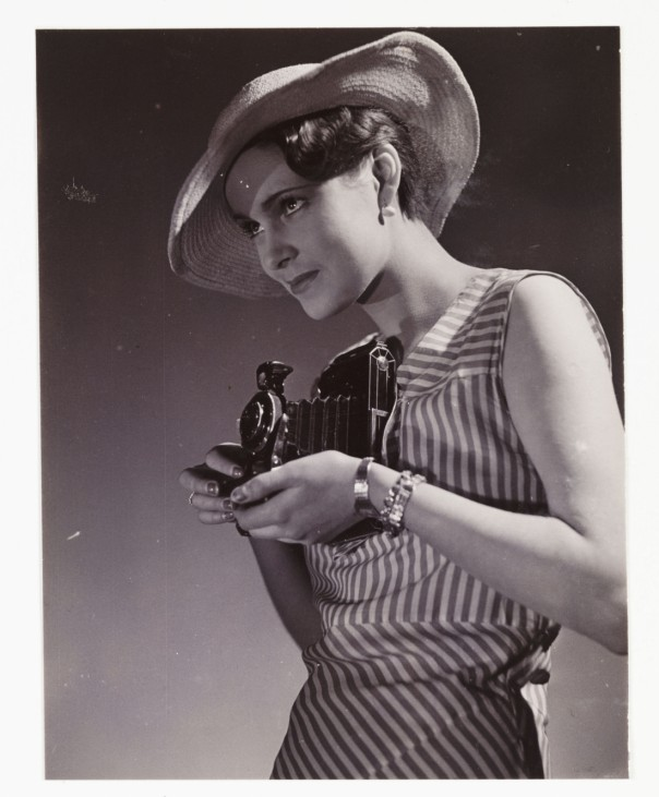 Woman in hat taking photograph using a folding roll film camera, c 1920s.