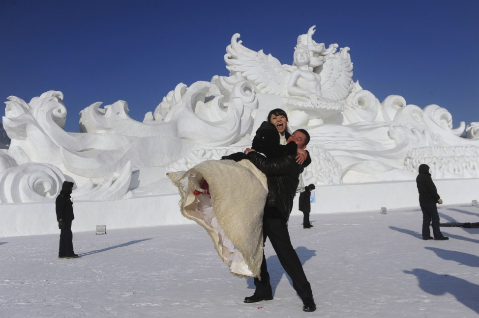 A man lifts his wife in front of a snow sculpture after a group wedding ceremony in Harbin