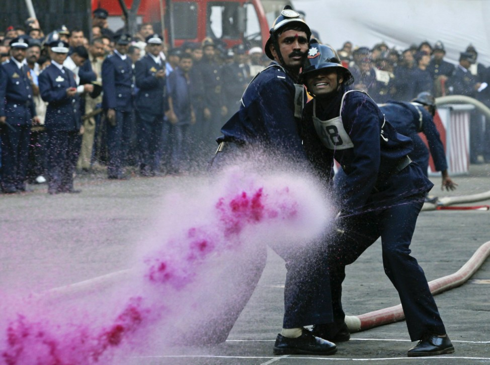 Firefighters aim coloured water at a target during the annual fire drill competition in Mumbai