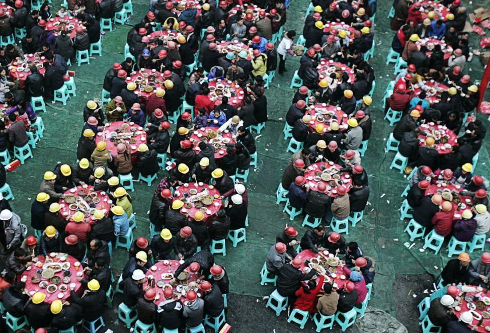Migrant workers have an annual meal at a local construction site in Chengdu