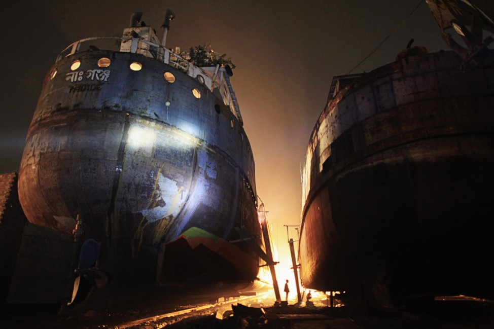 Workers work at a shipbuilding yard next to Buriganga River in Dhaka