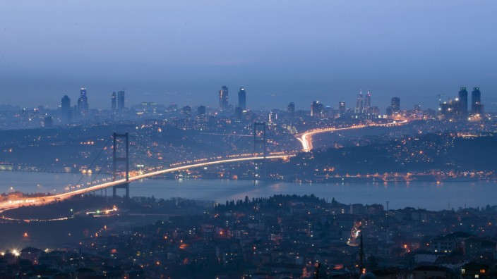 The Bosphorus Bridge is illuminated by the flood of traffic during rush hour, between the two sides of the city across the Bosphorus Straits