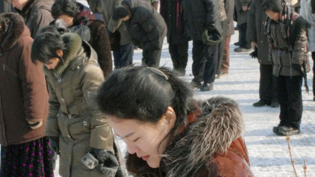People take part in a silent tribute during a national memorial service to mourn late leader Kim Jong-il in Pyongyang