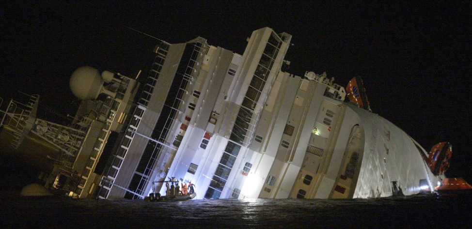 Rescuers are seen next Costa Concordia cruise ship that ran aground off the west coast of Italy at Giglio island