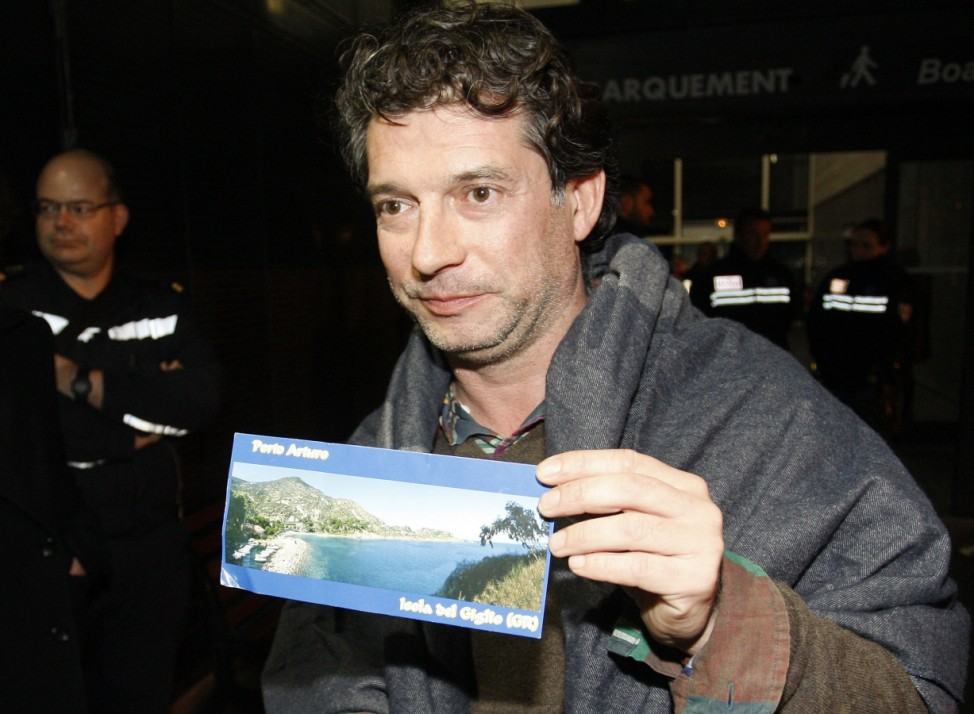 A surviving passenger of the Italian cruise ship Costa Concordia shows a postcard of his travel as he arrives at the cruise's terminal of Marseille harbour