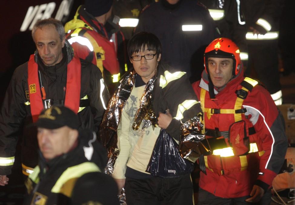 A South Korean man is helped after been rescued with his wife from Costa Concordia cruise as it ran aground off the west coast of Italy at Giglio island