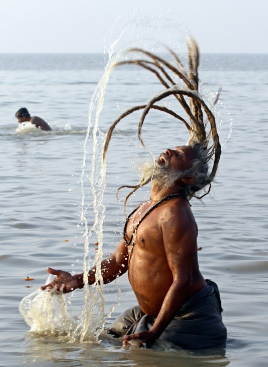 A 'Sadhu' takes a holy dip at the confluence of the river Ganges and the Bay of Bengal at Sagar Island