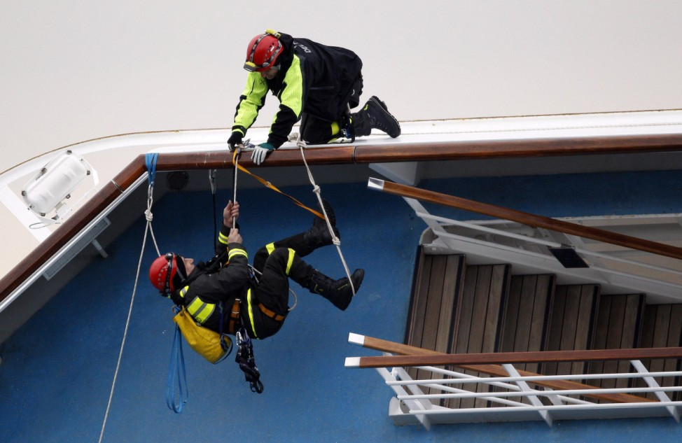 Rescue workers climb on the Costa Concordia cruise ship that ran aground off the west coast of Italy, at Giglio island
