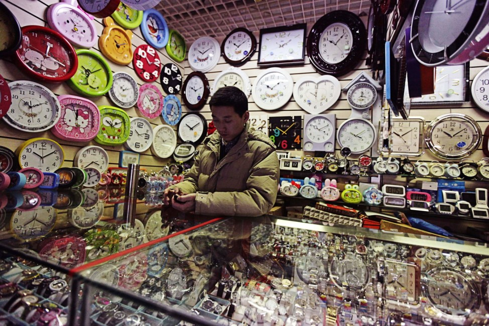 A clock and watch vendor plays with his mobile phone as he waits for customers at a market in Beijing