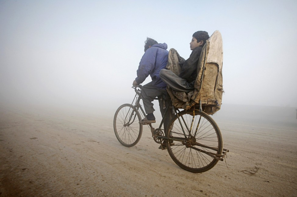 A boy rides on the back of a bicycle amid dense fog on a cold morning in Lahore