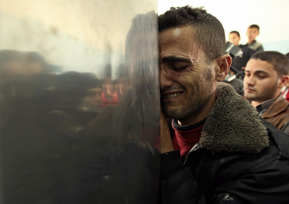A Palestinian man reacts upon the arrival of the body of a man, killed by an Israeli strike, at a hospital in Beit Hanoun